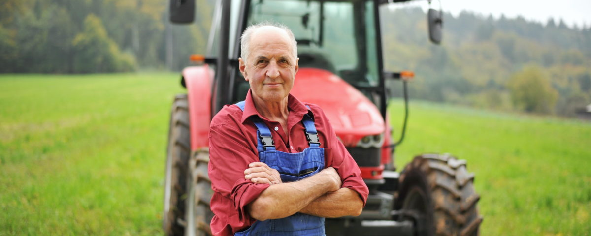 farmer standing in front of tractor