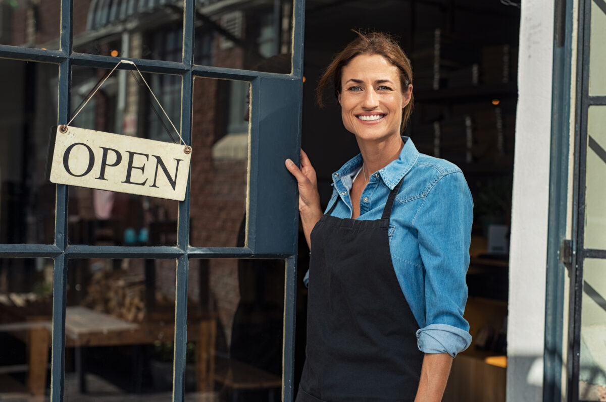 woman at shop door, open sign