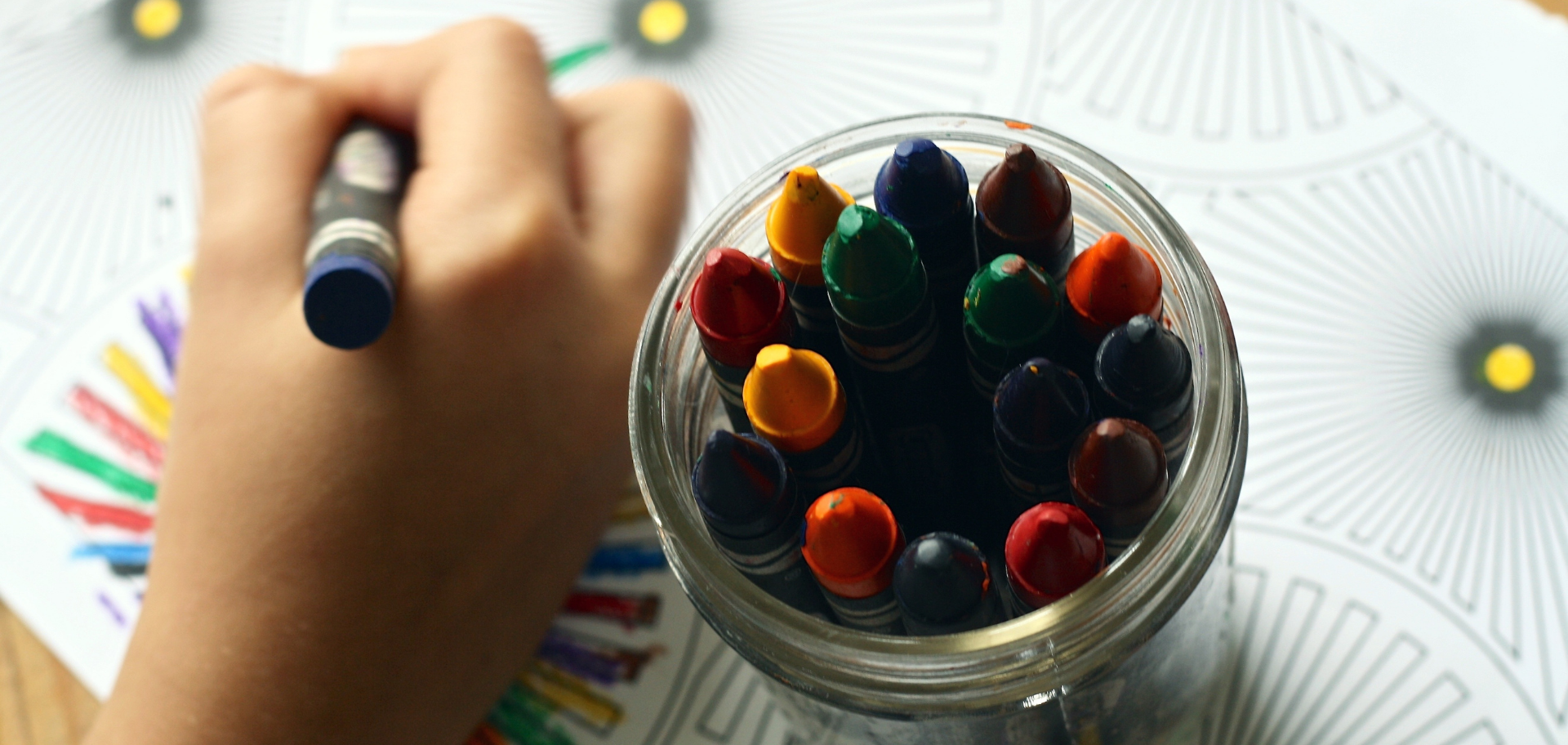 childs hand with jar of crayons